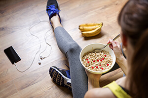 Woman Sitting on Floor Eating Cereal